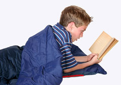 boy reading in a sleeping bag