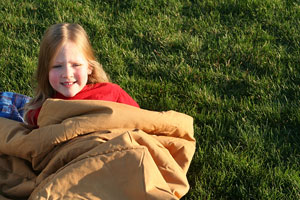 girl in a sleeping bag on a lawn